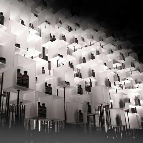 Eight hundred resin boxes are arranged atop steel rods of varying lengths, creating the sense that each box is ascending at its own pace, as if being drawn upward by an invisible thread.