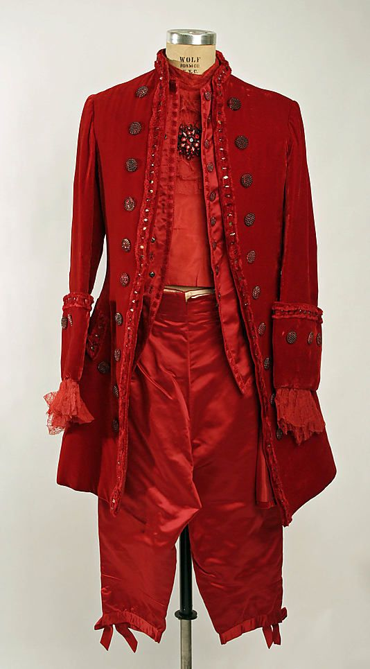 """Man's red velvet and satin """"Devil"""" fancy dress costume by Brooks Costume Company, American, 1953. Includes breeches, dickey, vest, coat, red stockings and shoes, and colonial-style wig with horns."""