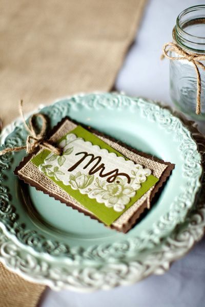 placecards (sorry -- no link!)  Looks like brown fabric, burlap, scrapbook paper, tied up with twine.