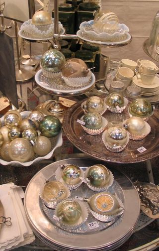 from Patina Green..vintage Christmas balls in silver cupcake papers on decorative trays