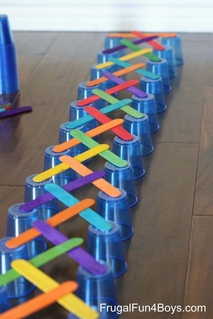 Remove the first cup & they start falling in a domino effect: 4 Engineering Challenges for Kids - with Cups, Craft Sticks, and Cubes.