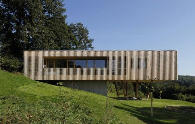 Poised over the edge of a hill in Hutten, Austria, Juri Troy Architects designed this residence to be both cost effective and passive. By lifting the home up over the land below, it employs a tiny footprint for its 100m2 living zone. Built out of local prefabricated timber, the home features a heat pump with ground collector, ventilation and heat exchange system, photovoltaic panels on the roof and wood wool insulation to 60cm - all creating a home with minimal energy output.