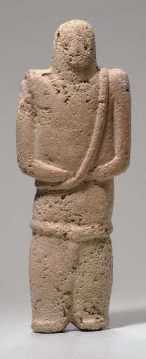 South Arabian stone figure, Bronze Age, 3rd-2nd millenium B.C. The abstract figure standing with the arms folded across the waist, the shoulders sharply angled, a raised ridge encircling hips, perhaps a belt, stylized genitalia prominent, a groove between the short legs, toes slightly protruding, face spade shaped and off set from cylindrical head, the nose triangular, 29.2 cm high. Private collection
