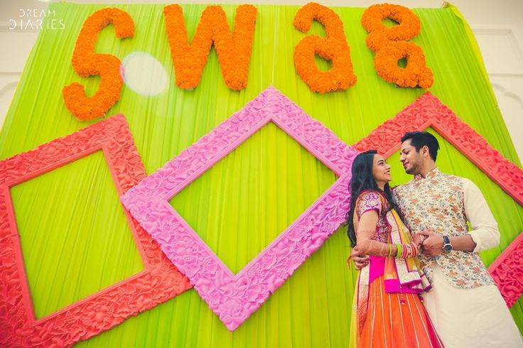 pink and peach Colourful photo frames with marigold letters swag on a lime green wall | Indian wedding photo booth ideas | fun wedding photos | Dream Diaries | The ultimate guide for the Indian Bride to plan her dream wedding. Witty Vows shares things no one tells brides, covers real weddings, ideas, inspirations, design trends and the right vendors, candid photographers etc.| #bridsmaids #inspiration #IndianWedding | Curated by #WittyVows - Things no one tells Brides | www.wittyvows.com