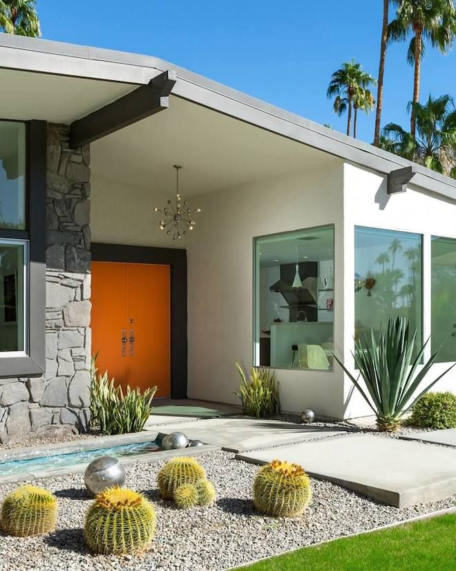 A midcentury entryway with an orange door, stone-covered walls, and landscaping with cacti at a home in Palm Springs.