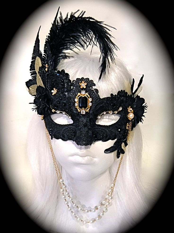A Venetian style masquerade mask that is black lace adorned with brushed gold gems and jewels. The mask has a double pearl necklace piece that hangs under the chin for extra elegance! There are black rhinestone gems, ostrich feathers, black glittered trims and vintage mesh gold leaves on both sides of this mask. Black velvet vintage yo yo flowers are special features and the mask ties with black silk ribbons. Your mask will arrive in a beautiful keepsake box.  All of the pieces you see in…