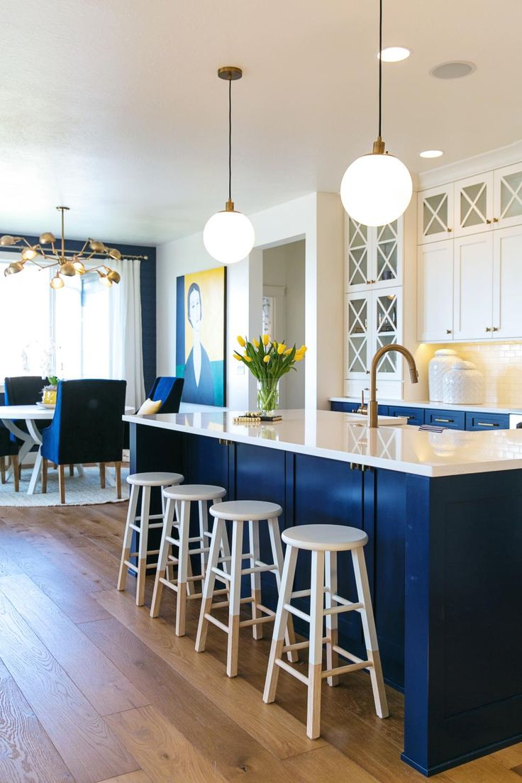 This kitchen is a comfortable space that still looks classy and refined. Navy blue and white juxtapose perfectly to create a clean-feeling room perfect for cooking and gathering with friends. The space features both a kitchen island with stools and eat-in dining table surrounded by comfy armchairs.
