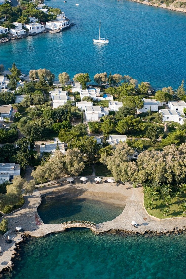 The whitewashed bungalows are surrounded by lush gardens. Agios Nikolaos, Greece  #Jetsetter