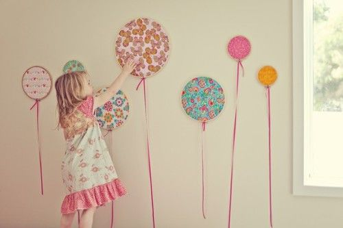 Use cross stitch hoops, stretch fabric across and add a ribbon for some cute balloons in child's bedroom.