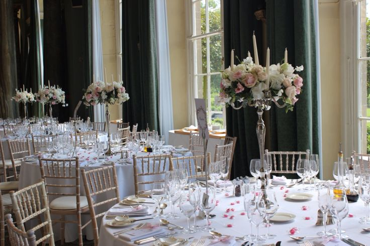 Romantic candelabra designs created by wild orchid wedding flowers at Woburn sculpture gallery, blush and white wedding flowers.  Roses, sweet pea, lisianthus, hydrangea