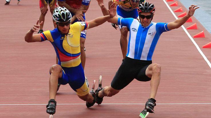 O colombiano Pedro Causil e o argentino Ezequiel Capellano disputam o primeiro lugar na linha de chegada da patinação de velocidade