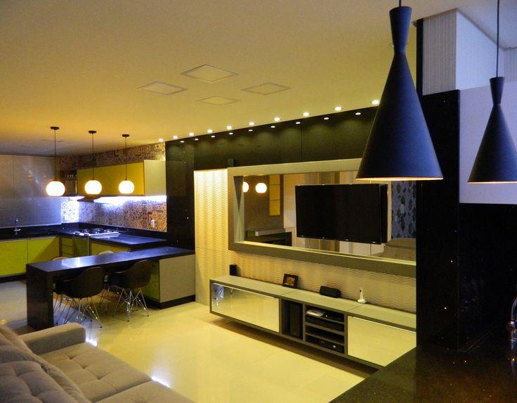 Ambiente integrado com sala e cozinha, bancada em silestone preto stellar separando os ambientes, iluminação em led, pendentes amarelos, cozinha com vidros amarelos e home tv com detalhes em espelho. Muito moderno.