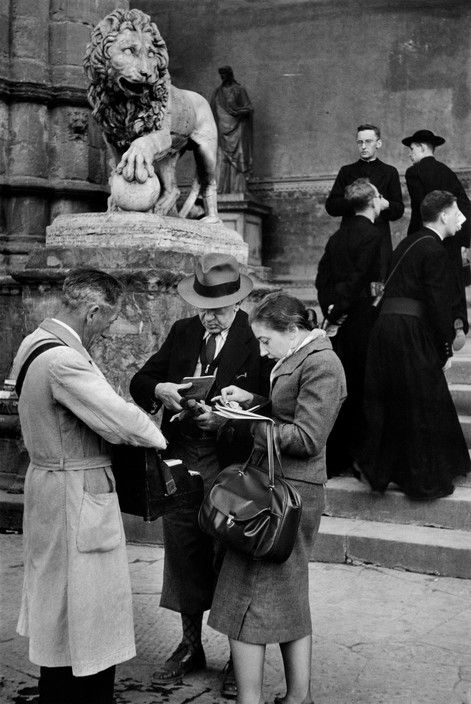 Magnum Photos - Henri Cartier-Bresson // ITALY. Tuscany. Florence. 1953. Piazza della Signoria. German tourists buying postcards with german marks.