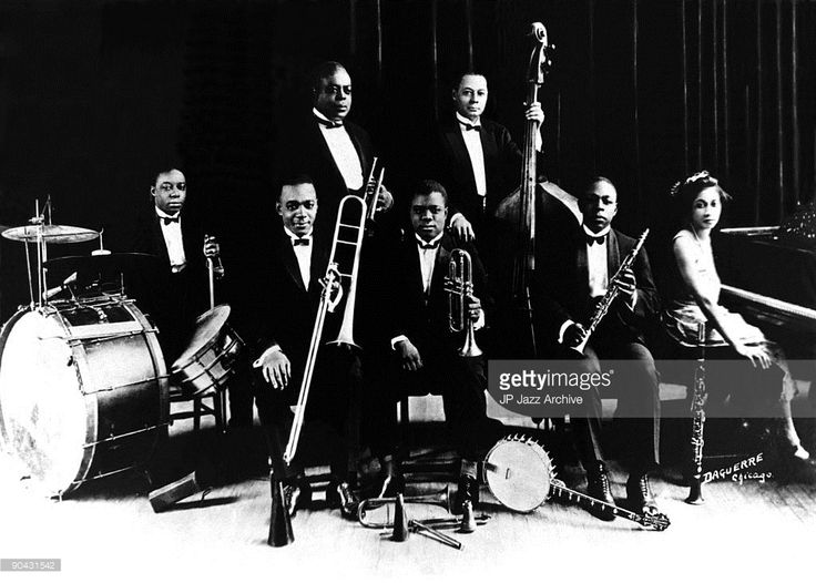 King Oliver's Creole Jazz Band pose for a studio group shot in the early 1920s, with (L-R) Baby Dodds, Honore Dutrey, King Oliver, Louis Armstrong, Bill Johnson, Johnny Dodds and Lil Harding.
