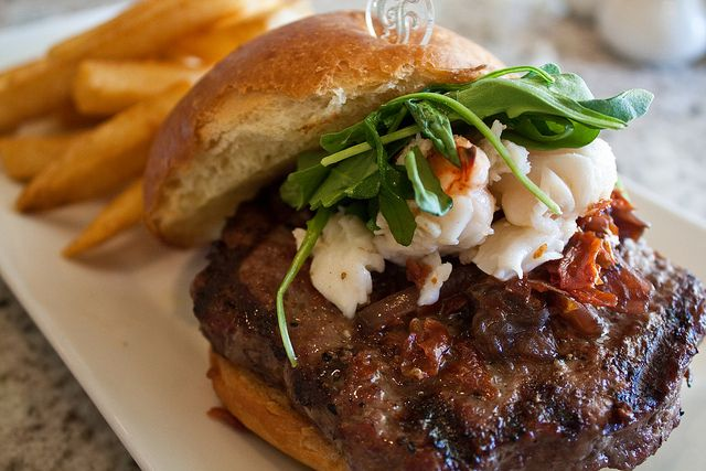 Surf and turf on a bun. The Grand Floridian burger. Here is the description: Angus chuck burger, buttered poached lobster with red onion marmalade, crispy prosciutto and arugula on a Brioche bun. You will die.