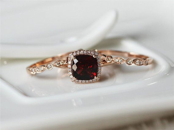 Gorgeous Garnet Engagement Rings   Crafted with 14k rose gold, this cushion cut garnet ring has all the elements of elegance and grace. The halo of bright white diamonds enhance the beauty of the center stone giving you a ring that truly shines.