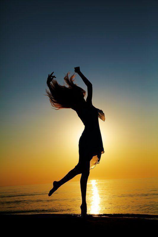Stock Bild von Mädchen tanzt am Strand bei Sonnenuntergang. natürliches Licht … – Katie