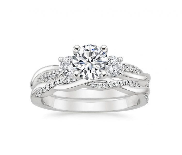 ''Atena'' Three Stone Petite Twisted Vine Diamond Bridal Set A nature-inspired twist on the classic three-stone ring.  This design features entwined vines shimmering with pavé diamonds. Mounting type: Four-Prong Average width: 2.5 mm 2 Round Cut Diamonds 3 mm each 0, 20cts Total Extra Small Diamonds: 58-64 Included Side Band