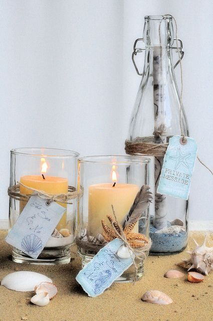 Candles in hurricane lamps, with feathers and starfish, and a message in a bottle