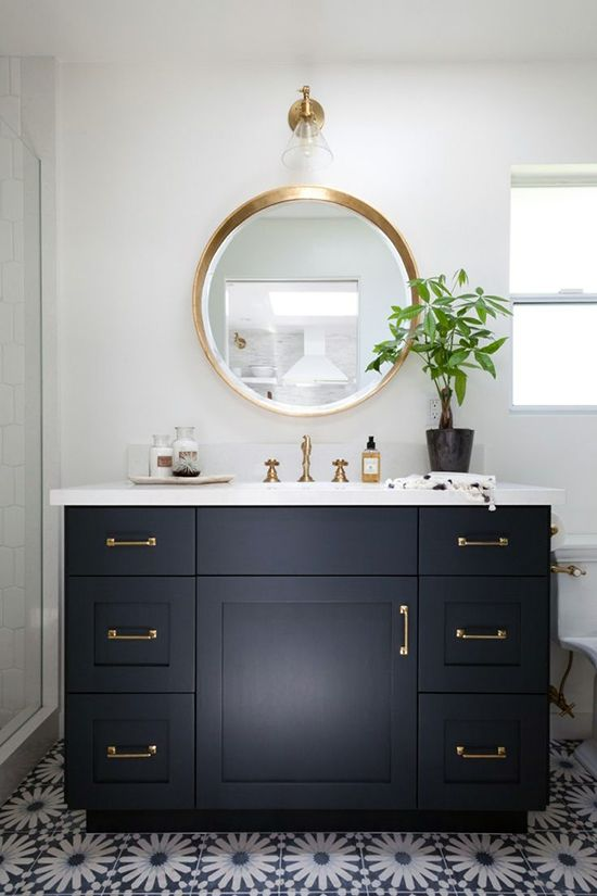 Transitional powder room with round gold mirror and single brass and glass…