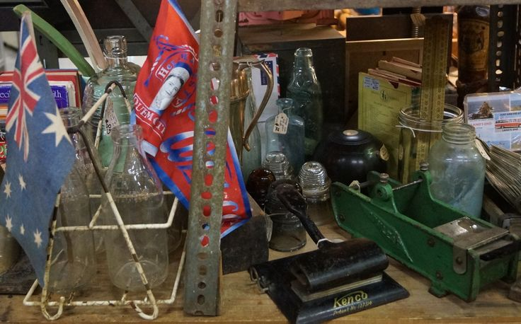 Rare vintage finds: flag from the 1958 Queen Mother's visit, 1958 Australian flag from the same visit, wire milk bottle crate & 4 one pint bottles, black cast iron Kenco hole punch, green cast iron gum tape dispenser, rusty iron, coloured glass bottles. Available in Vintage Design Shop in Melbourne.