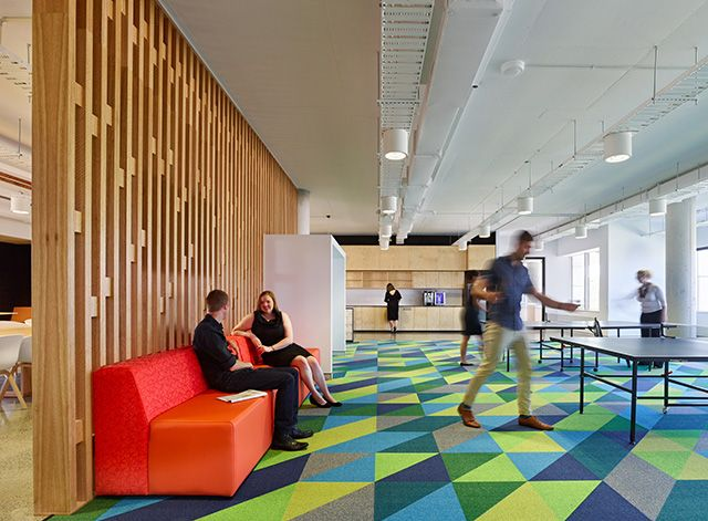 Geometric Flooring - The GE headquarters in Springfield, Queensland. For the social hub, the heart of this design, a Designer Jet custom carpet with a geometric pattern in bright green hues was created. #customcarpet #commercialspaces #godfreyhirst