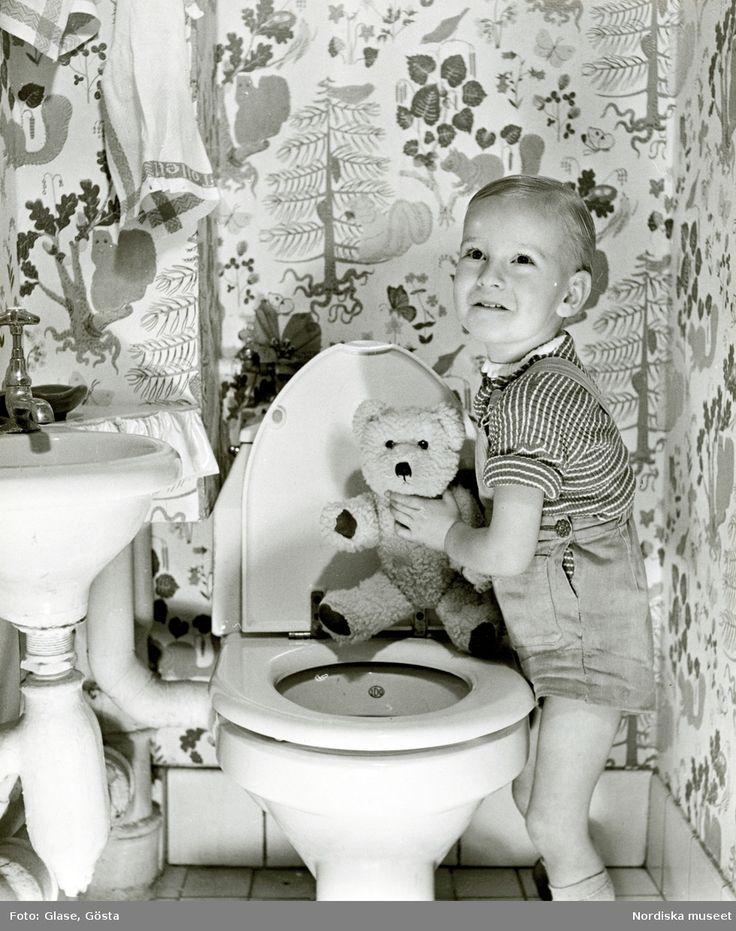 Ett barn i randig tröja och hängslebyxor med nalle i handen, vid en toalett. @ DigitaltMuseum.se