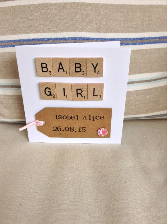 A personalised New Baby Girl card. White card with scrabble letters spelling Baby Girl. Underneath is a brown luggage tag decorated with a pink