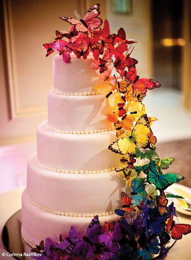 A Butterfly Rainbow. A simple white cake, with butterflies of all shapes and sizes (bought from a craft store) ascending in their varied shades of color… Definitely eye-catching. Simple yet Bold, and if you are doing your cake yourself, easy! :-)