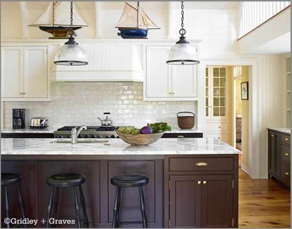 Lovely nautical kitchen. Love the dark & white cabinets, brass hardware, marble counter, subway tile, and sailboats on top of the cabinets.