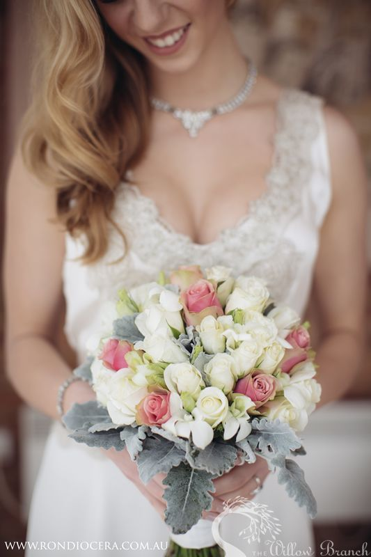 A natural-stemmed bouquet of roses, lisianthus and dusty miller matched her thin, ribboned hair-circlet.