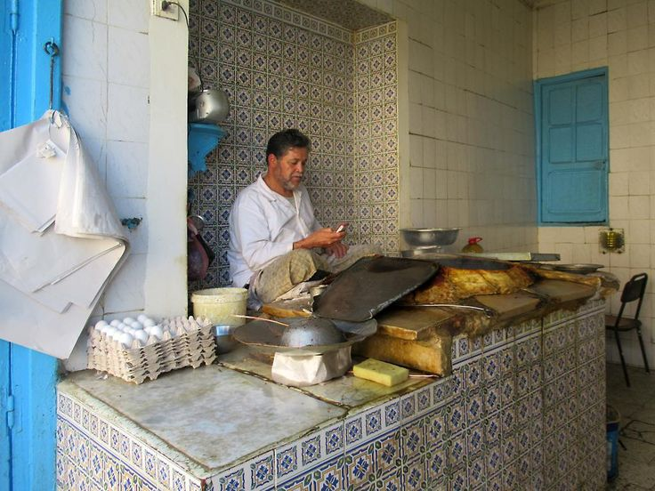 A traditional fast food maker in Kairouan, Tunisia, checks his cell phone for messages.