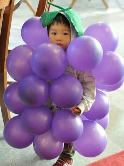 Dressed up for Halloween in purple balloons and a green leaf hat as a cluster of grapes - So-so cute!