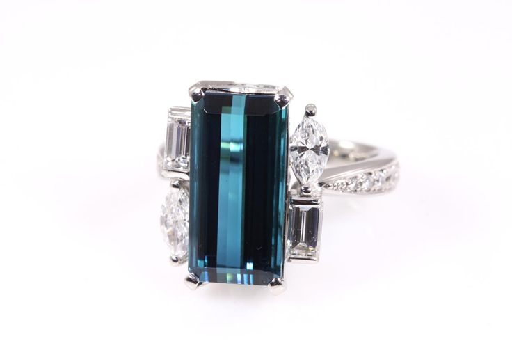 Blue Tourmaline and Diamond Ring with an emerald cut Blue Tourmaline of 7.29ct and Baguette, Marquise & Round Brilliant cut Diamonds totalling 1.19cts (Estimated Grading: G VS-SI). Platinum. Ring size M - can be resized by a maximum of 3 sizes up and down. With Certificate. (Pre-owned)