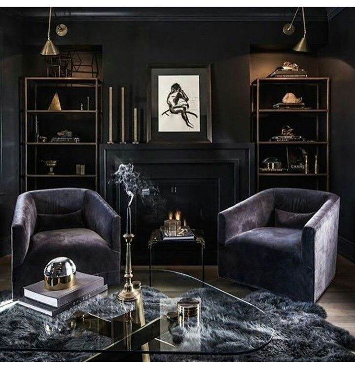 living room features a black fireplace topped with a nude abstract sketch and modern brass candle holders flanked by niches filled with brass