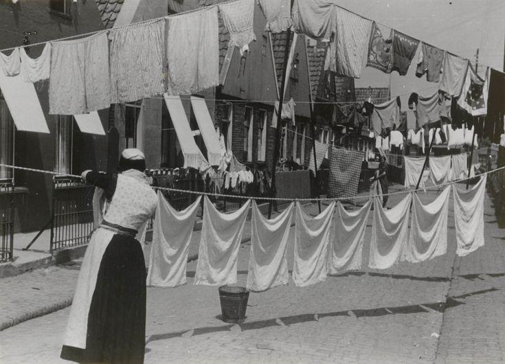 Een vrouw in Urker streekdracht hangt de was op. Diverse waslijnen zijn over de straat gespannen. #Urk