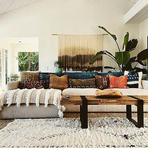 The magic of textured rugs and blankets, a rustic wooden table, and vivid earth-coloured pillows. Rustic bohemian decor.