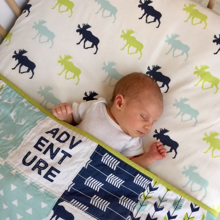 Baby Henry looks warm and comfy under his Bear Creek Crib Set Etsy: ShopHarperAndFinn Moose, antler, arrows, woodland, bears, mint, green, navy, crib bedding, crib bedding set