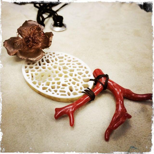 Collana con medaglione in osso, ramo di corallo, madrepora e fiore in rame battuto a mano, montato su argento e cordino di alcantara