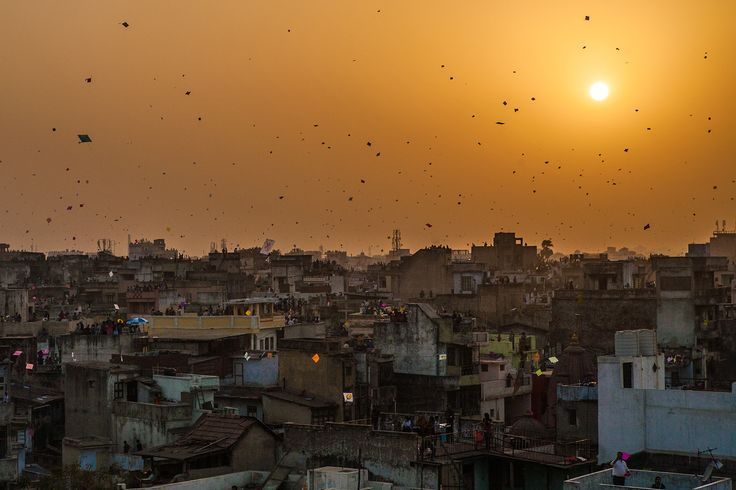 People gathered on terraces or rooftops of their houses everyone flying kites and the sky covered with tiny colourful dots of kites for the festival of Makar Sankranti or Uttarayan in the old Khadia area of Ahmedabad in Gujarat, India