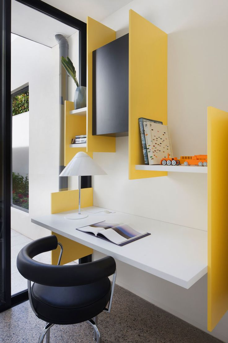 This small and modern study has bright yellow supports that hold the white wall shelves and floating desk in place.