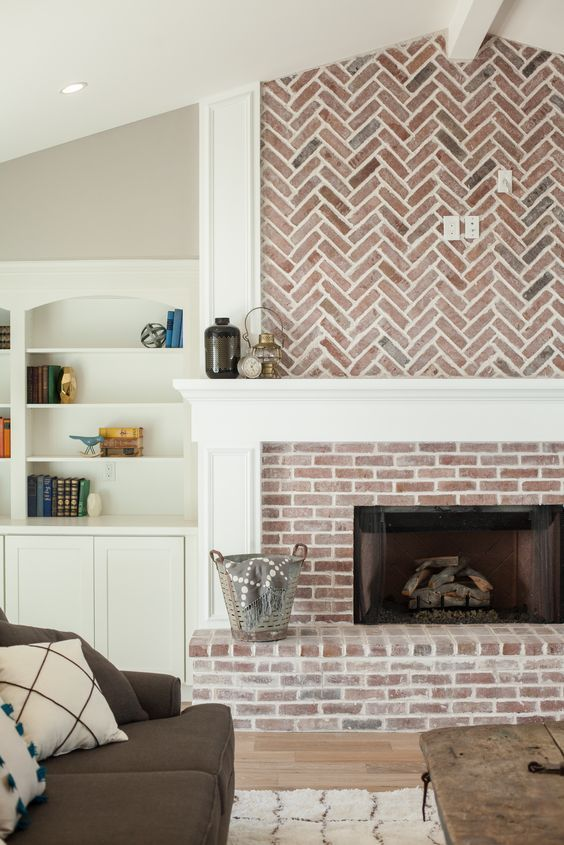 Fireplace with herringbone pattern brick work and built in shelving - by Rafterhouse.