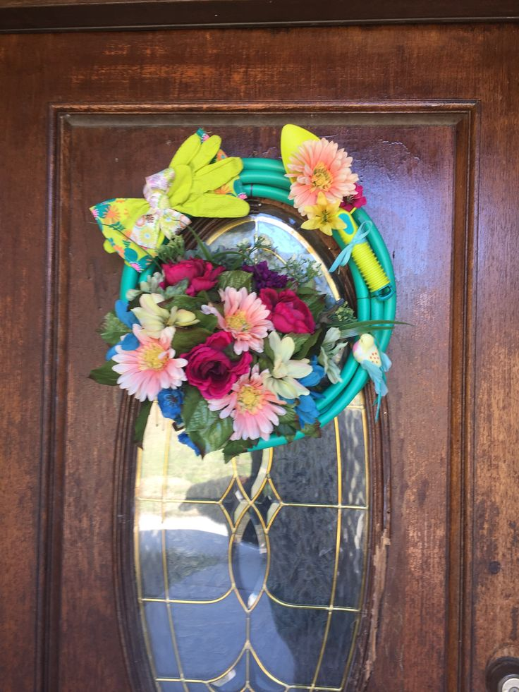 i made this garden hose wreath with a 6 garden hose a 2 pair of gardening gloves a plastic toy garden trowel and a 5 bouquet of faux flowers all