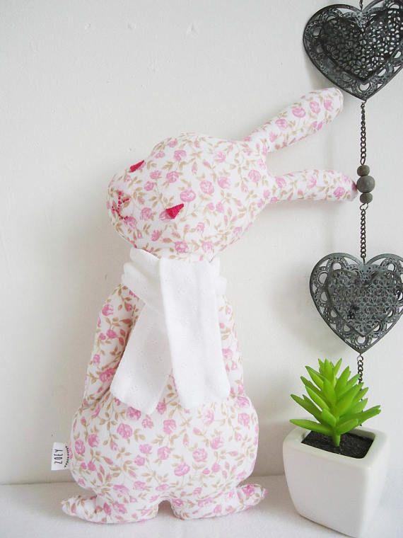 Ce petit lapin blanc et rose (n°2 sur la photo) trouvera sa place par exemple sur une étagère, un fauteuil, un bureau, une commode dans la chambre de votre enfant. Il est en coton blanc imprimé de fleurs rose poudré ; les feuillages sont ocre beige. Lécharpe est en jersey blanc à petites