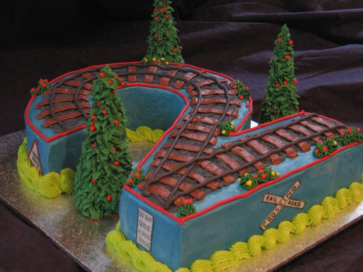 "Toby's 2nd Birthday Train Cake - This cake began as a 14"" x 11"" madiera cake, which I carved into a ""2"". Cake was covered in various colours of buttercream., including tracks etc. The trees are cones covered in RI. All train signage was made from edible rice paper and Wilton edible markers. The client added a real toy Thomas the Tank Engine and carriage onto the BC tracks after collecting the cake. Thank you for looking!"