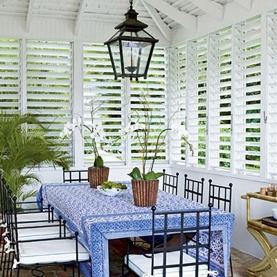 Dining in island style: ditch draperies and embrace the crisp lines of window shutters. Details such as white seat cushions, a patterned tablecloth, and delicate orchids add just enough softness against iron chairs and a hanging lantern in this lavender dining room. Coastalliving.com