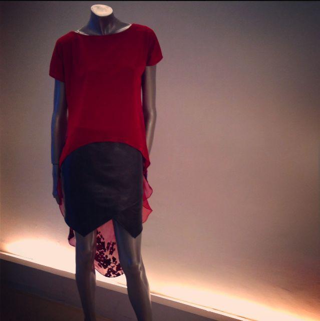 Falda cruzada en piel color gris y blusón high-low de seda en color rojo con transparencia en la espalda.