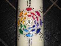 Kerzen mit Regenbogen-Fischen und Kreuz