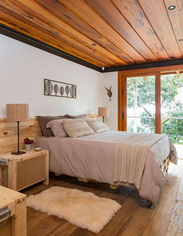 Decoração de casa de campo com madeira. No quarto de casal luz natural, porta de madeira e vidro, e decoração neutral.
