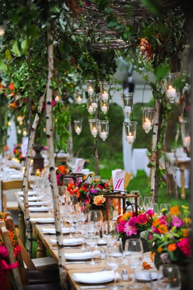 Georgeous outdoor tablescape in bright pink, orange and green wth lanterns and candles.